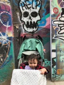 a baby sits in a stroller in front of graffiti of a skull that says help.