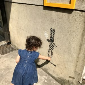 A baby touches a picture of a rabbit that is spray painted on a wall.