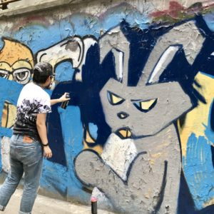 a person spray painting a wall. The wall has a graffiti image of a rabbit.