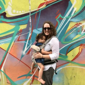 A woman wearing a baby in front of a spray painted wall.