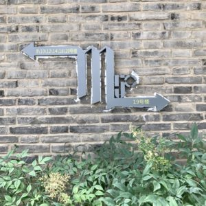 A sign with the letter M made of metal.