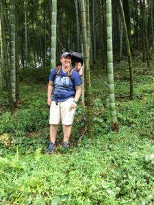a woman wearing a baby in a backpack stands in a bamboo forest