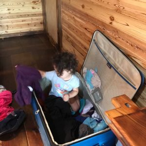 a child sits in a suitcase surrounded by clothes